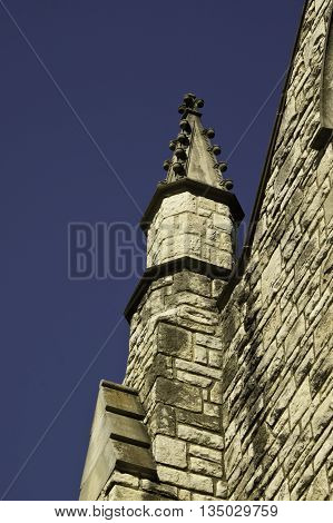 A beautiful old stone church steeple against a gorgeous blue sky.