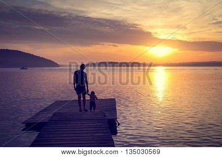 Silhouettes of Young Father with His Little Baby Standing on the Pier and Watching Sunset by the Sea. Happy Family Lifestyle. Dad and Son Concept. Toned Photo with Copy Space.