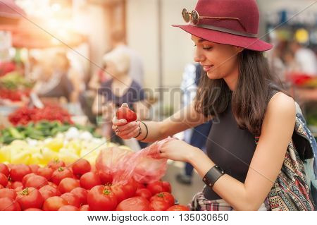 A young woman buying fruits and vegetables at a weekly market. Healthy diet