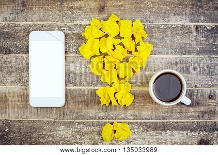 Idea concept with crumpled paper lightbulb coffee cup and blank white smart phone on antique wooden table. Mock up