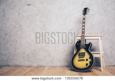 Electric sunburst guitar against wooden stool in room with parquet flooring and concrete wall with copy space