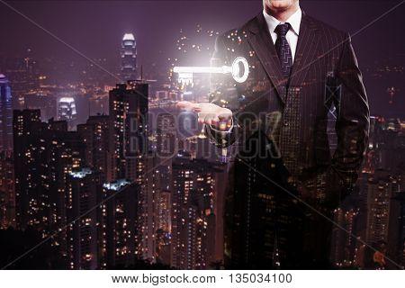 Businessman holding levitating key on abstract illuminated night city background. Double exposure