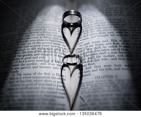 Wedding rings casting heart shaped shadow over Bible