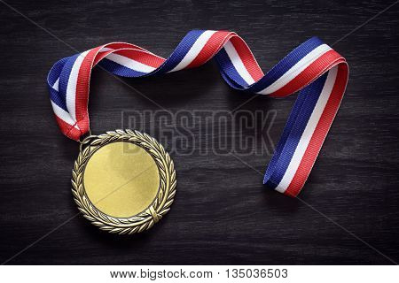 Gold medal on black wood background with blank face for text, concept for winning or success