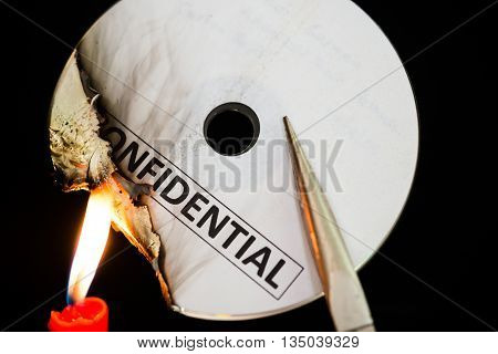 burning a confidential compact disc with candle in dark SS
