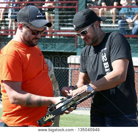 ARLINGTON, TX - APR 18: Recording artist Luke Bryan (R) and his tour manager Mark Sizemore at the ACM & Cabela's Great Outdoor Archery Event at the Texas Rangers Youth Ballpark on April 18, 2015.