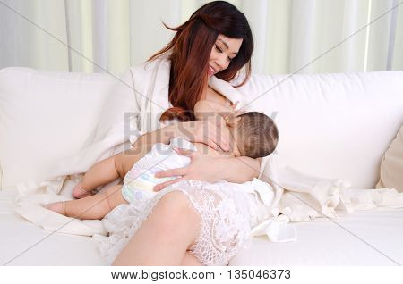 Asian woman breastfeeding her six months old baby boy poster