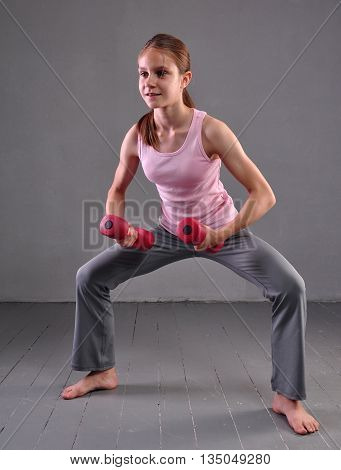 Portrait of teen age sportive girl exercising with dumbbells on grey background. Sport healthy lifestyle concept. Sporty childhood. Teenager child exercising with weights.