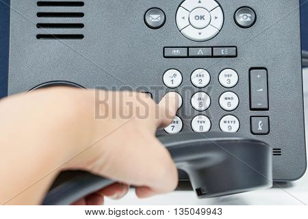 Dial the number pad of IP phone with human left hand
