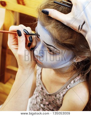 little cute child making facepaint on birthday party, zombie Apocalypse facepainting, halloween preparing, lifestyle people concept