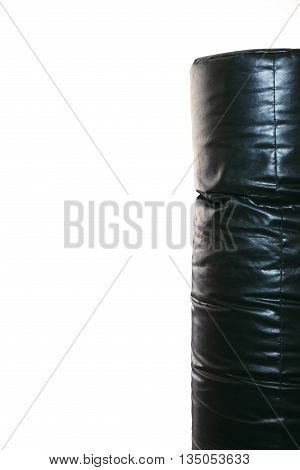 Black punching bag isolated on white. Cropped image of black punching bag on right side of picture. Vertical half of punching bag, isolated on white, copy space