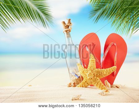 Empty glass and flipflops on beach, blur sea on background. Summer exotic relaxation concept. Copyspace for text