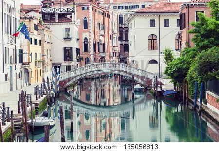 Bridge over canal in Venice Italy. Traditional architecture also reflected in the water