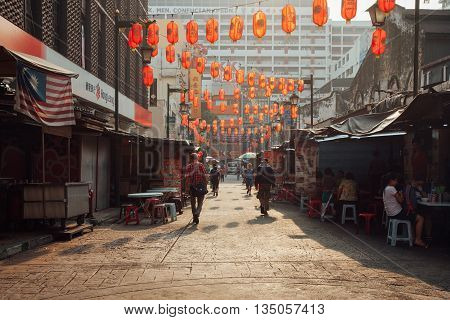 KUALA LUMPUR MALAYSIA - MARCH 17: People walking through Petaling Street while other eating at the street stalls in Chinatown during the morning hour Kuala Lumpur Malaysia on March 17 2016.