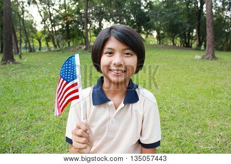 Young girl smiling and waving American flag in the park