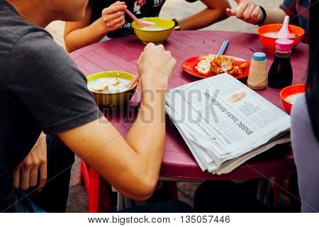 Kuala Lumpur Malaysia - March 17 2016: Group of young people having a breakfast with congee and Youtiao in Chinatown Kuala Lumpur Malaysia on March 17 2016.