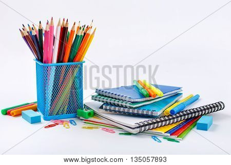 Notebook and copybook stack with metal holder pencils pens paper clips sharpener and eraser on a white background. Back to school concept