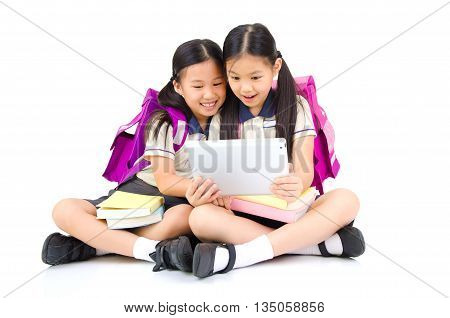 Asian primary students sitting on the floor using tablet