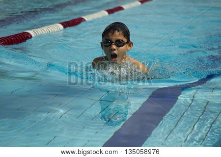 Young chinese boy wearing goggles and cap swimming breaststroke in a pool
