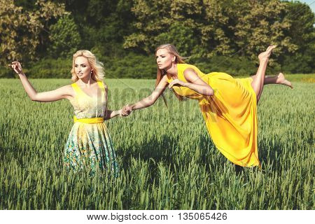 Two charming women are in the field. One woman levitates over the field and the other woman is holding her hand.