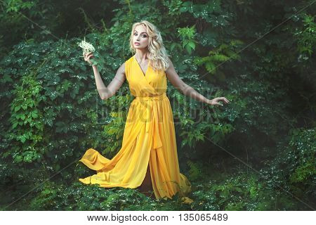 Charming woman is in the woods in her hand she holds a white flower. She looks like a fairy fairy.