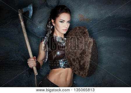 Medieval woman amazon holding a shield and an ax.