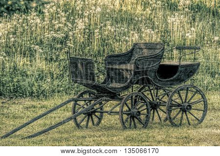 Old black and worn stage coach  in old  vintage photo style.