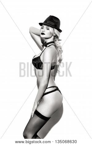 Sensual sexy blonde showgirl in tux and hat posing at wall black and white