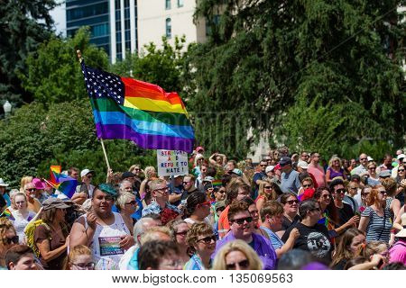 BOISE IDAHO/USA - JUNE 20 2016: Crowd of people under a large flag in support of LGBT during the Boise Pride Festival