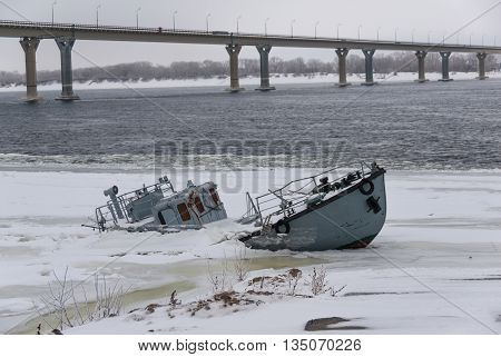 Sinking ship in a frozen river covered with ice