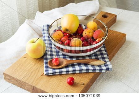 Composition of fruits and berries. Reason for the longevity is apples, cherries, apricots. Fruits and berries in a bowl on a checkered napkin on the table. Fruits and berries on a wooden cutting board poster