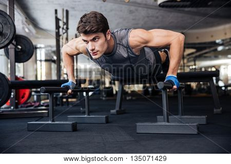 Portrait of a handsome fitness man doing push-ups at gym