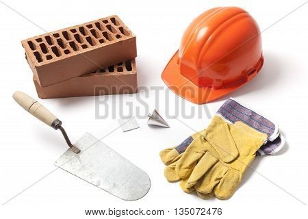 Several construction accessories trowel bricks plummet hard hat and gloves isolated on white background.