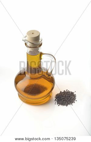 Mustard Oil Decanter with Mustard Seeds on White Background