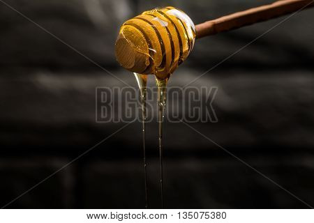 Honey dripping from a wooden honey dipper on dark background