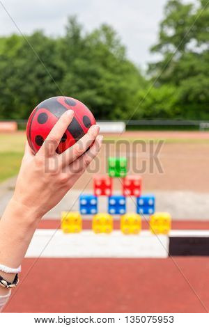 Girls arm with ball to throw at colored blocks as a game