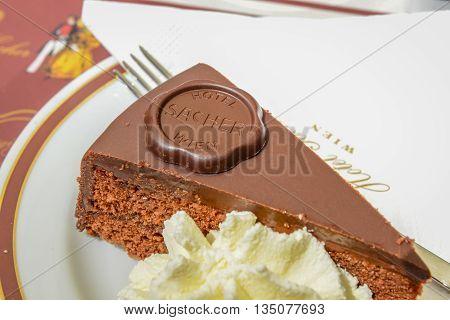 VIENNA AUSTRIA - JUNE 01. 2016: Original Sacher Torte with cream and fork at Sacher Cafe Vienna Austria Europe june 01 2016