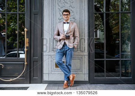 Full length of happy young man in funny round glasses standing and holding old vintage photo camera