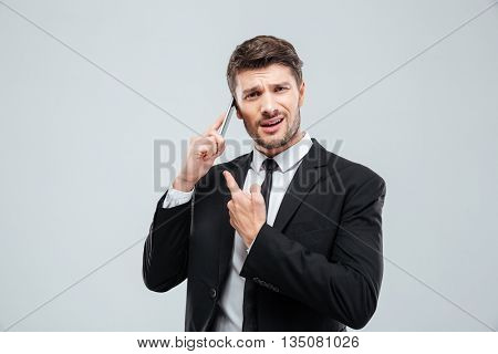 Confused young businessman talking on cell phone over white background