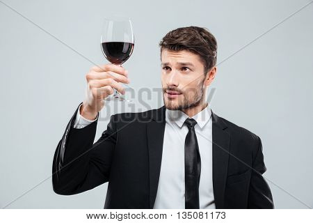 Serious young man sommelier in suite tasting red wine in glass over white background
