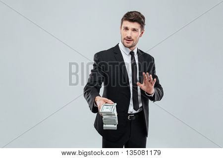 Attractive young businessman in suit and tie giving you money back over white background
