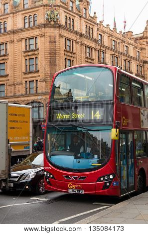 LONDON - OCTOBER 19 2015: Famous red double decker bus in front of the harrods store in the knightbridge district