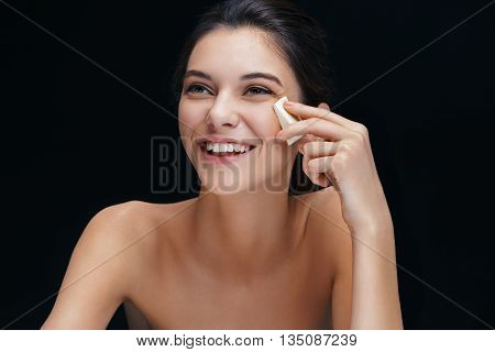 Young woman uses sponge for make up. Photo laughing girl of european appearance on black background. Youth and skin care concept
