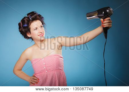 Young woman preparing to party having fun funny girl styling hair with hairdreyer retro style on blue