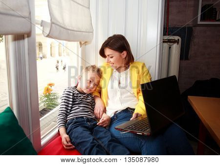 Happy mother and son looking at laptop at home by the window