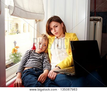 Mother and son looking at laptop at home in the room