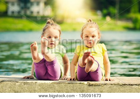 Twin girls are exercising on a lake shore