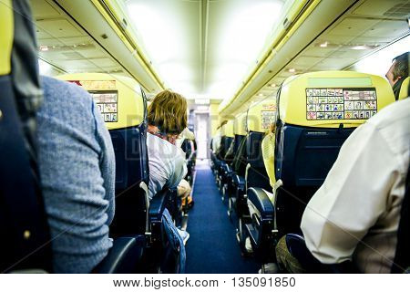 People sitting in commercial aircraft. Rows of sits on a low cost airlines passenger jet plane.