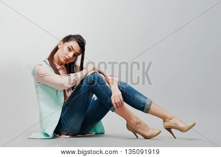 Sitting Portrait Young Brunette Girl Wearing In Pink Blouse, Turquoise Jacket, Ripped Jeans And Crea