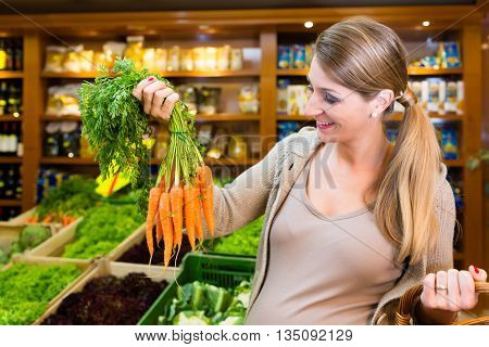 Pregnant woman buying healthy vegetables in grocer store